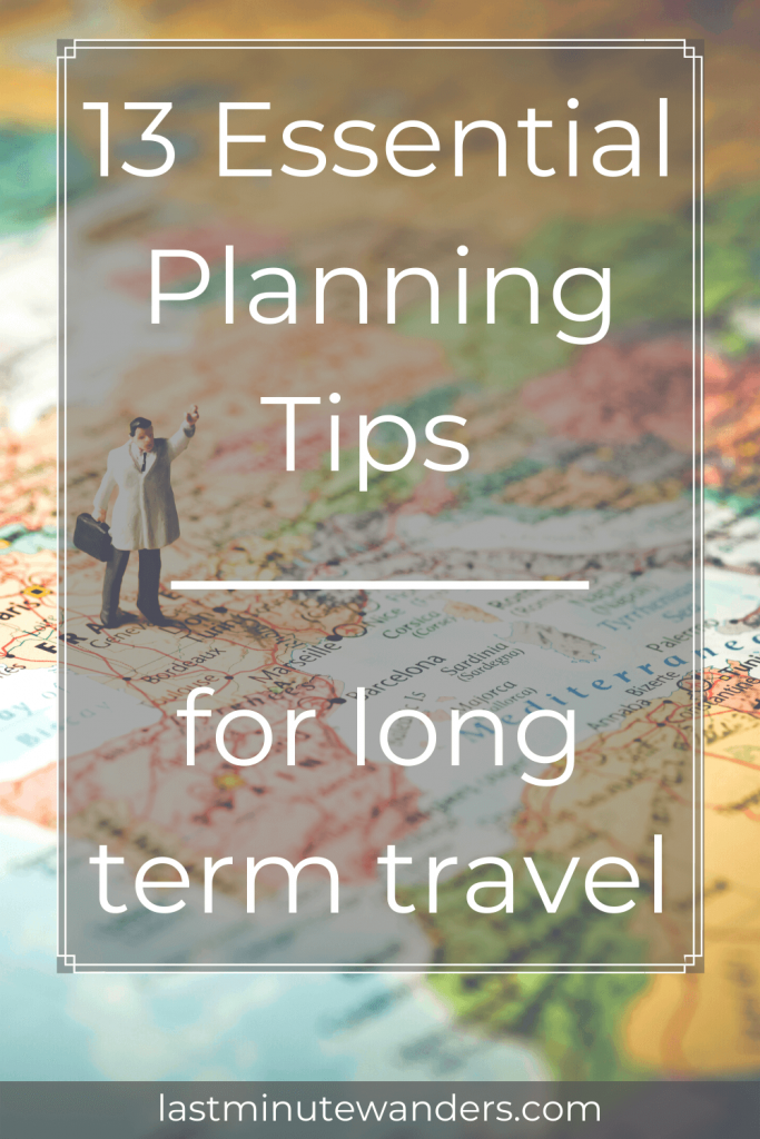 Small toy man with arm in air holding suitcase standing on large map with text overlay - 13 Essential planning tips for long term travel