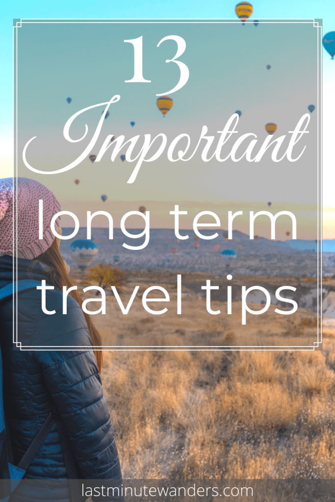 Woman looking across fields with many hot air balloons in the background with text overlay - 13 important long term travel tips