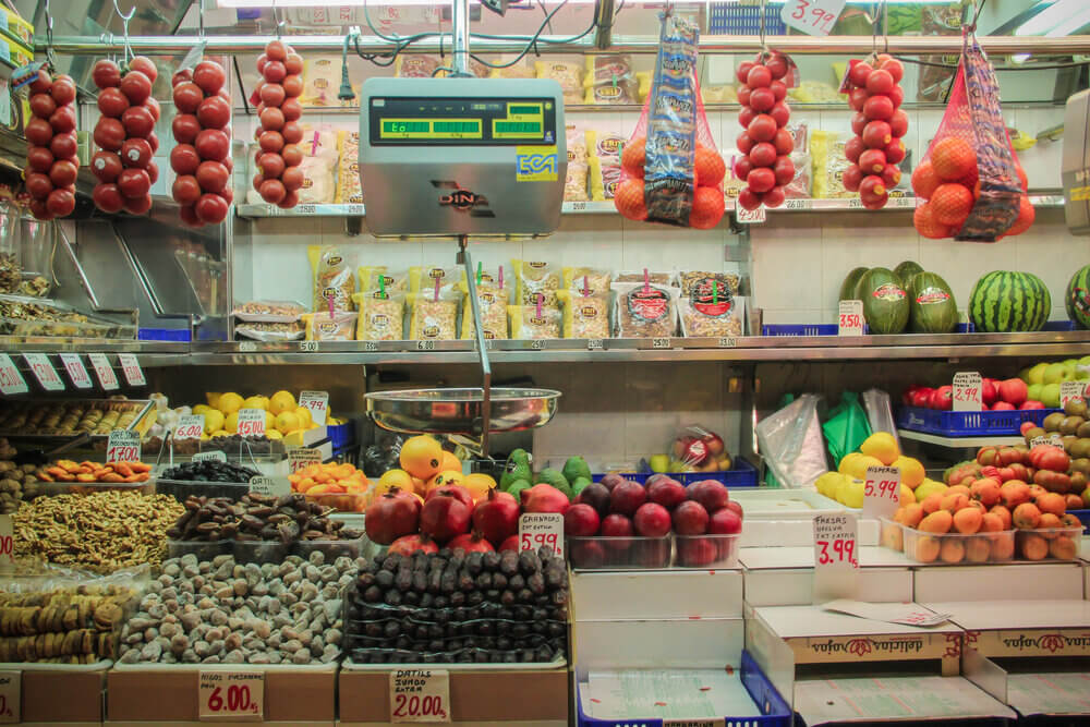 Front view of a small grocery shop with lots of fruit and vegetables on display