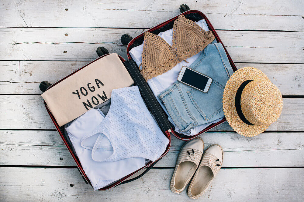 Open suitcase packed with woman's clothes with phone and sunhat