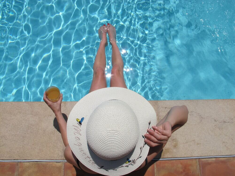 Aerial view of woman wearing a white sunhat by the pool with drink in hand