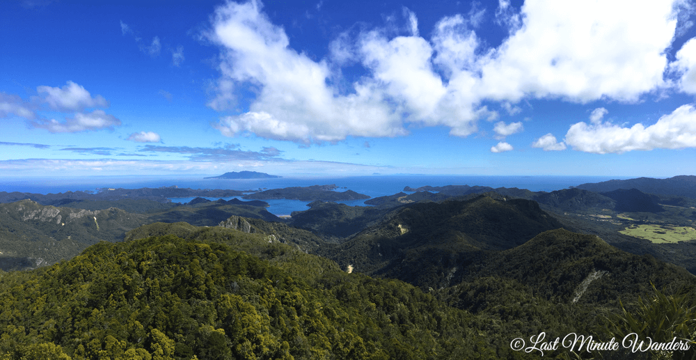 View from mountain summit of green hills and islands.