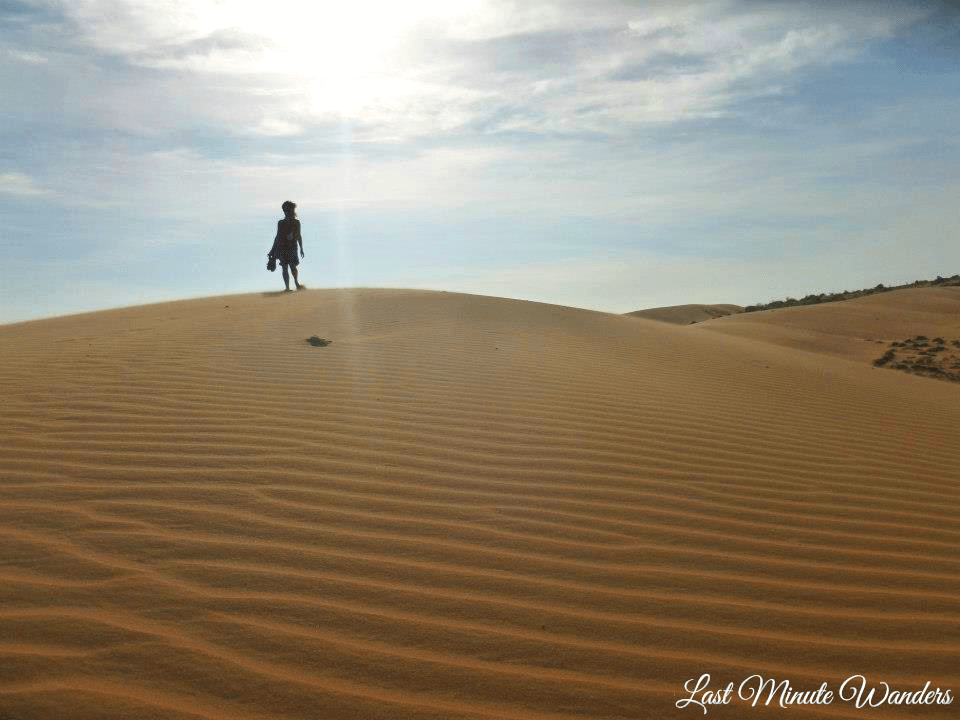 Woman silhouetted against sky on top of sand dune