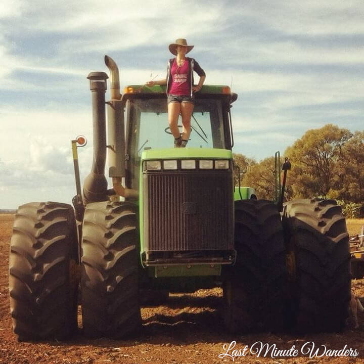 Woman standing on bonnet of farm tractor