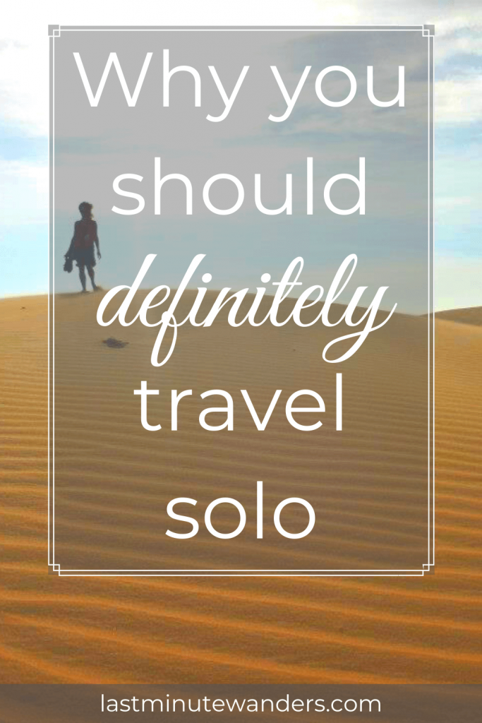 Silhouette of woman standing on top of sand dune with text overlay - Why you should definitely travel solo