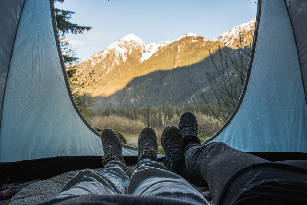 Two sets of legs in tent with view of mountains