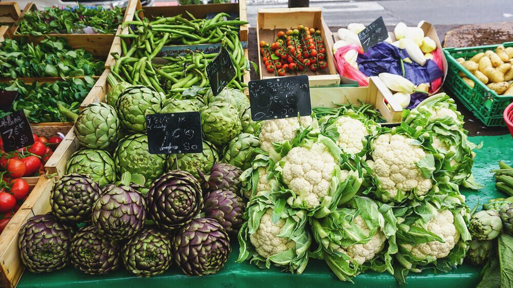 A variety of green vegetables on a market stall
