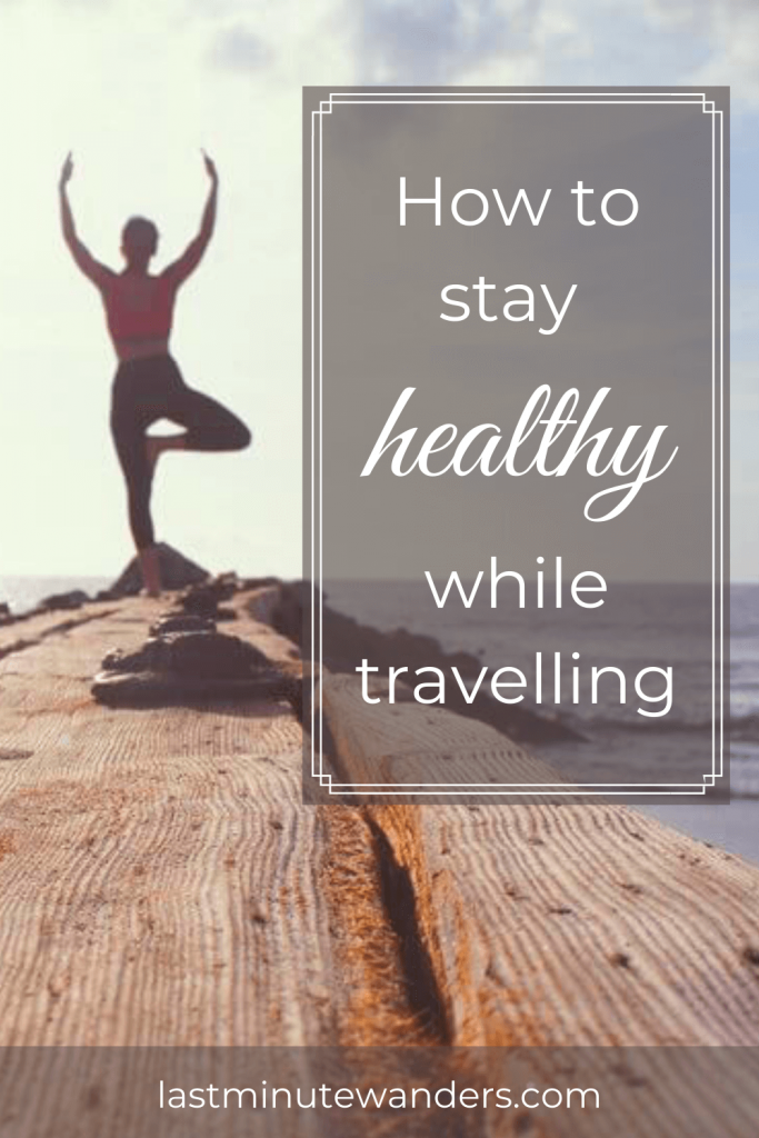 Woman doing yoga pose by sea with text overlay - Stay healthy while travelling