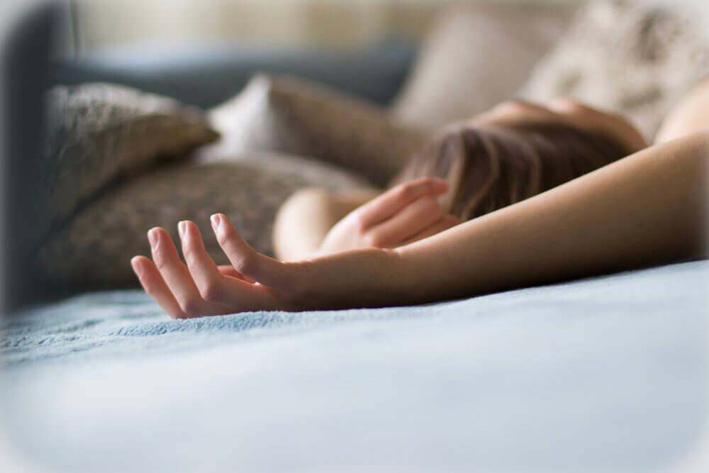 Close-up of woman's hands resting above her head on bed.