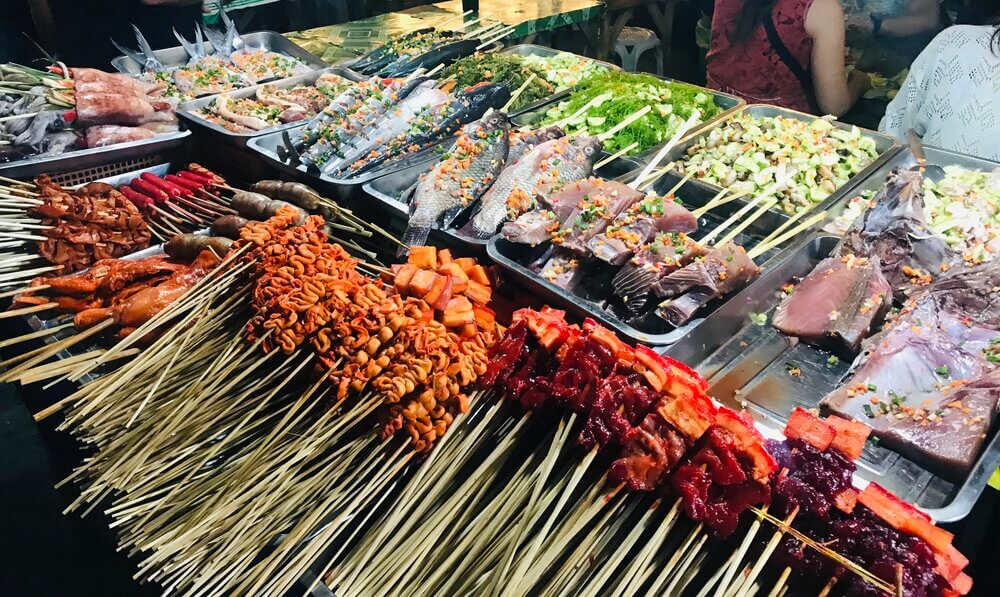 Food stall with meat and fish on sticks and vegetables.