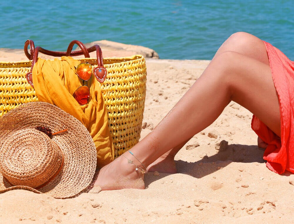 Woman's legs resting on sand near yellow bag and sun hat.