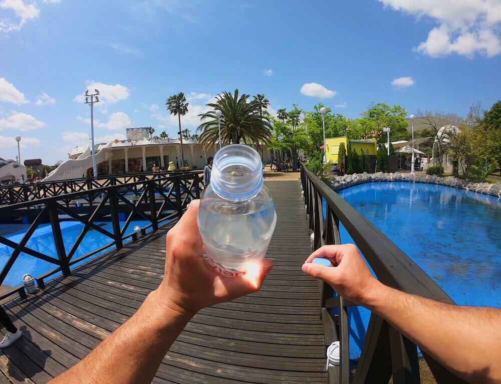 Person's point of view of their hands holding a plastic water bottle on a bridge over blue water.