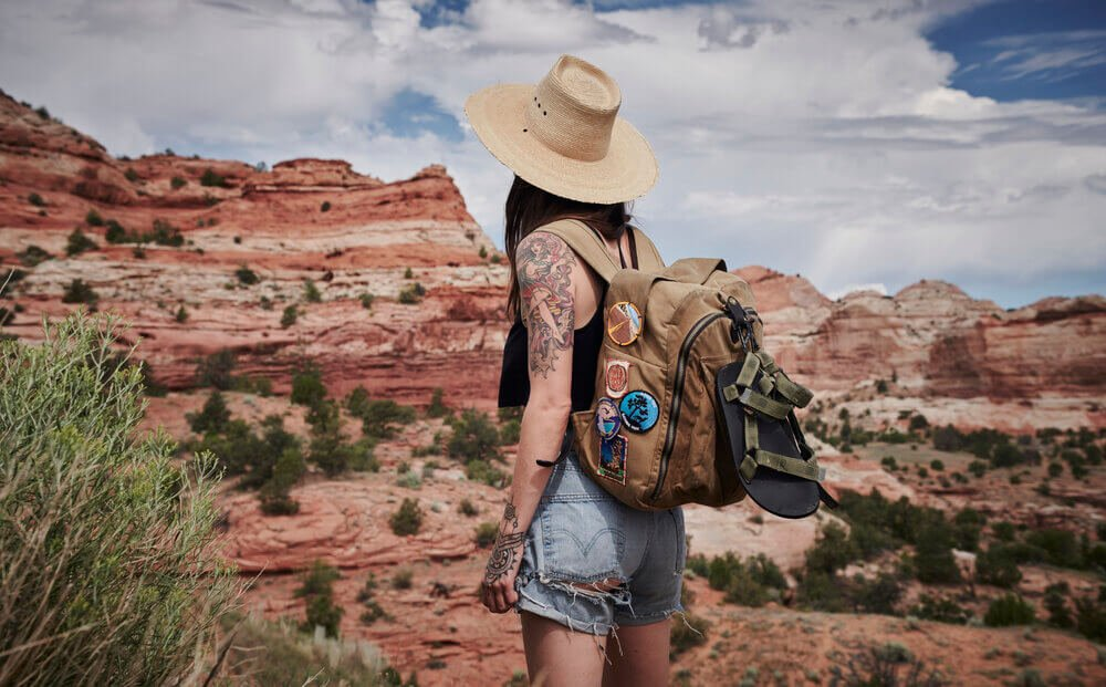 Tattooed woman in sun hat and backpack by red canyon