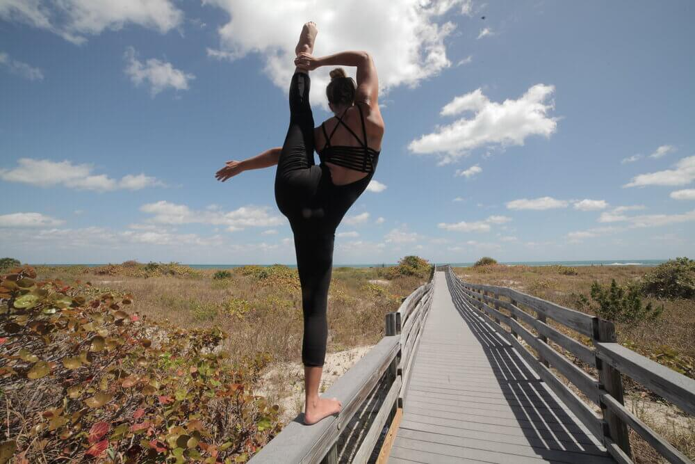 Woman standing on fence doing yoga pose while facing away from the camera.