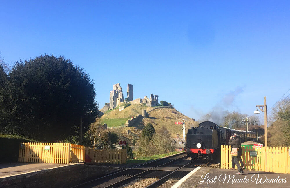 Steam train approaching past castle ruins