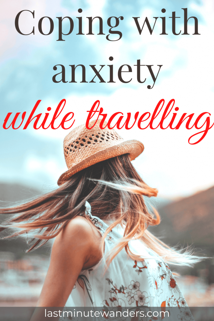 Woman wearing straw hat and white top spinning away from the camera with text overlay - coping with anxiety while travelling