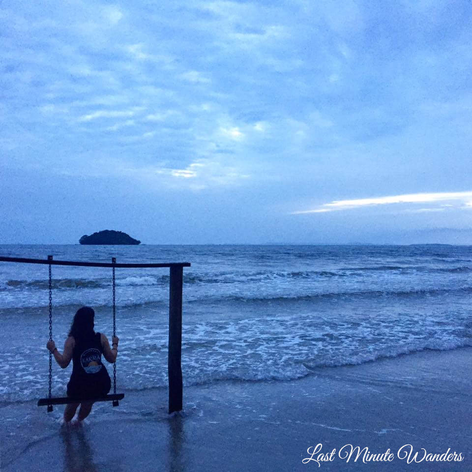 Woman sitting on swing on beach at twilight