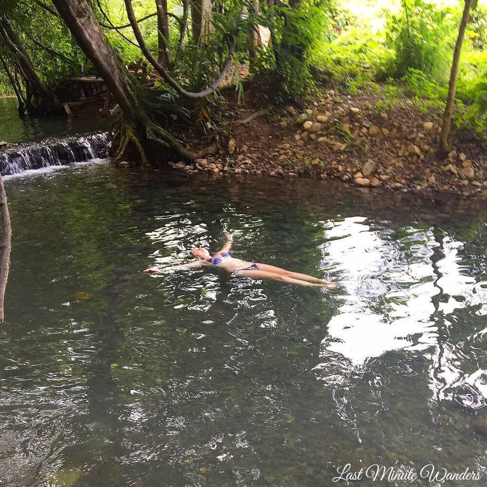 Woman floating in natural pool with trees behind.