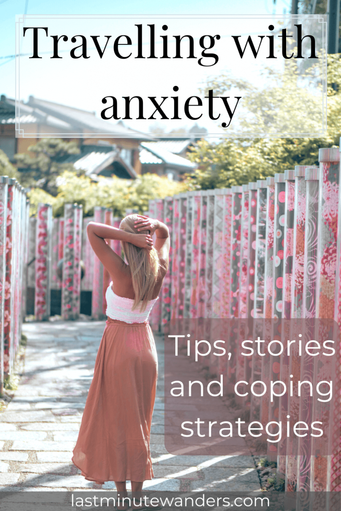 Woman holding hair while standing on pathway lined with pink pillars with text overlay - Travelling with anxiety: tips, stories and coping strategies