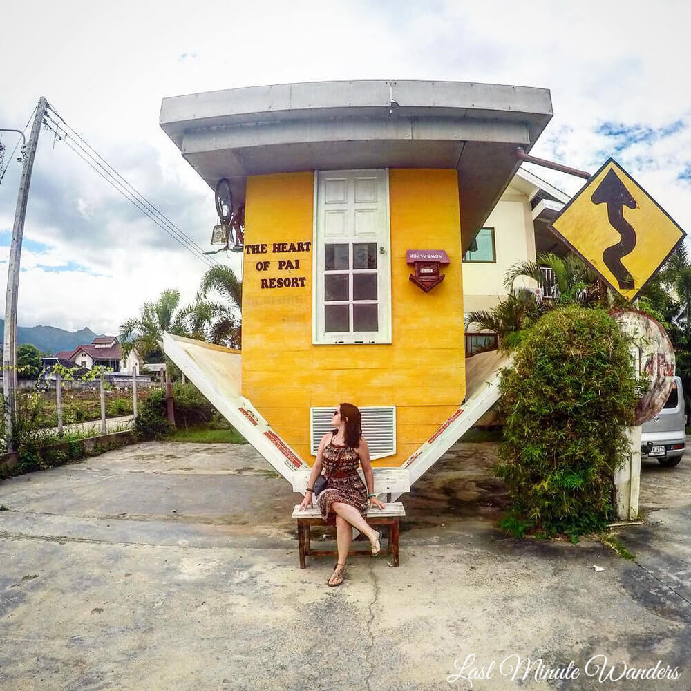 Woman sat on bench in front of upside down yellow house