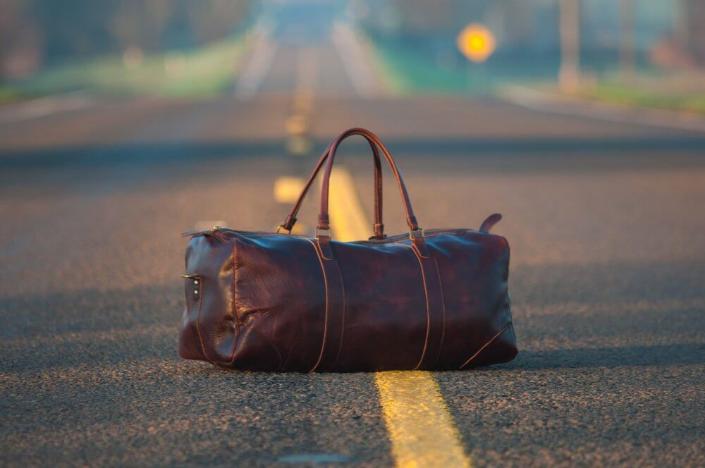 Brown duffel bag in road