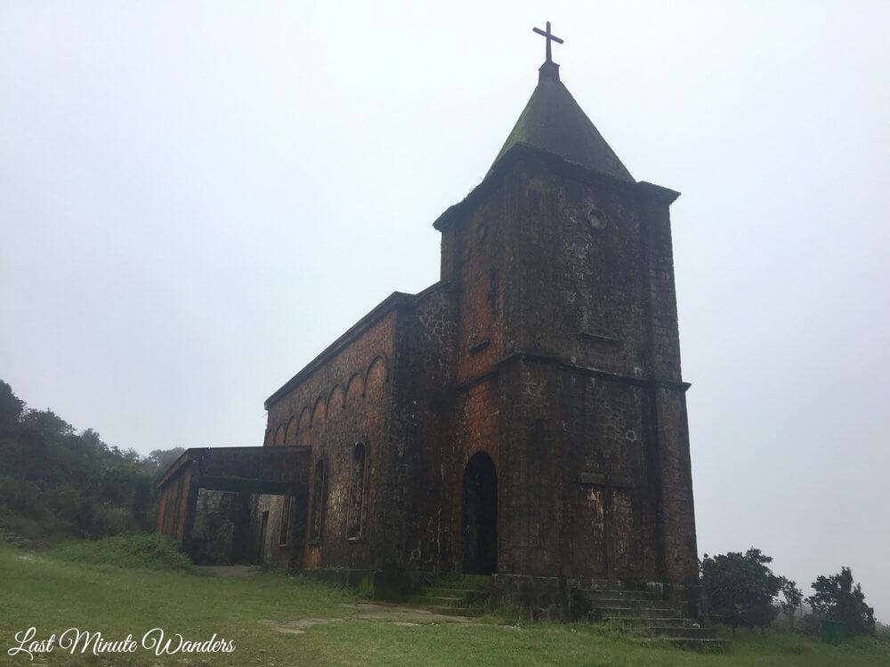 Abandoned catholic church against a grey sky
