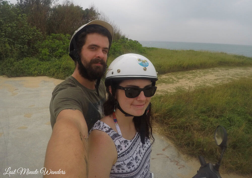 Couple in helmets on scooter by sea