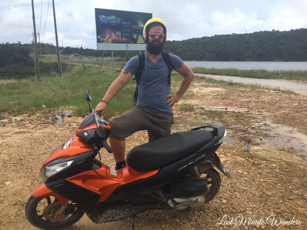 Man with stationary orange scooter