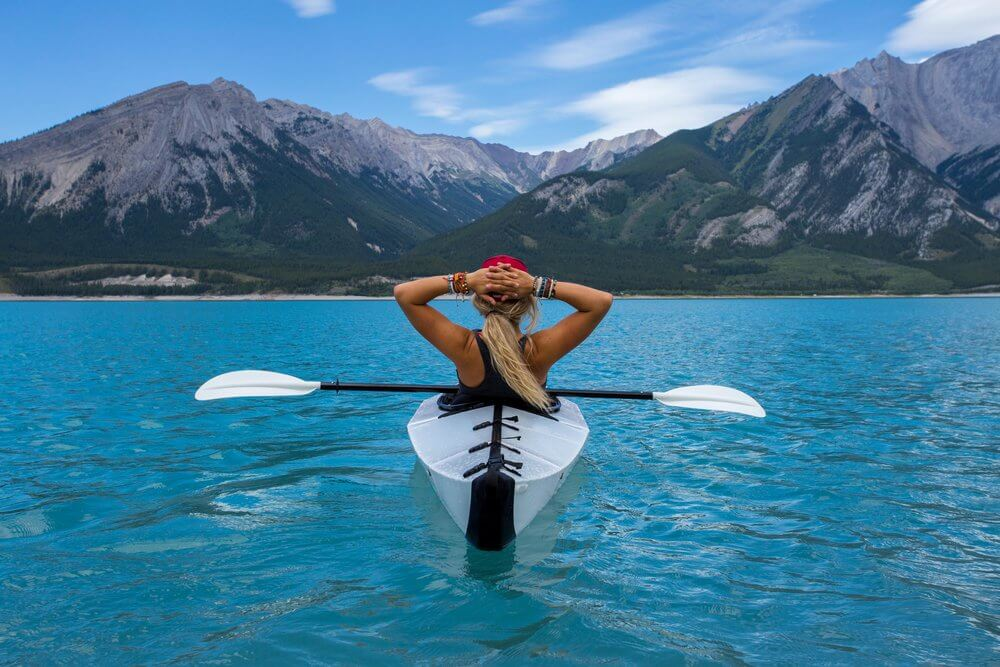 Woman sitting in kayak on water with mountain view