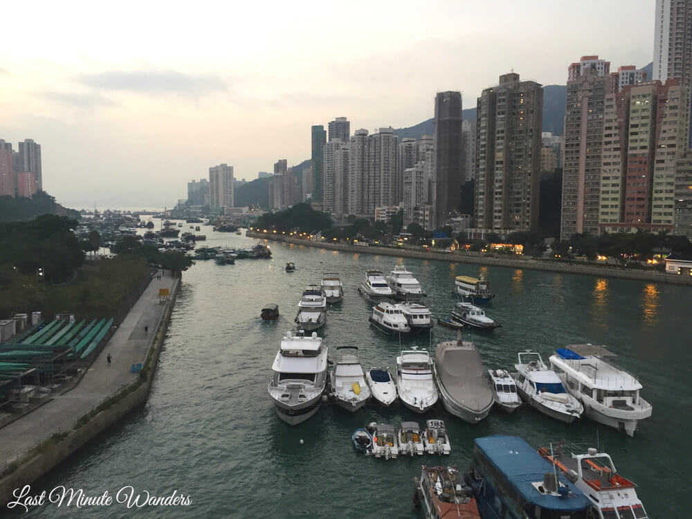 View of boats in river by high rise buildings