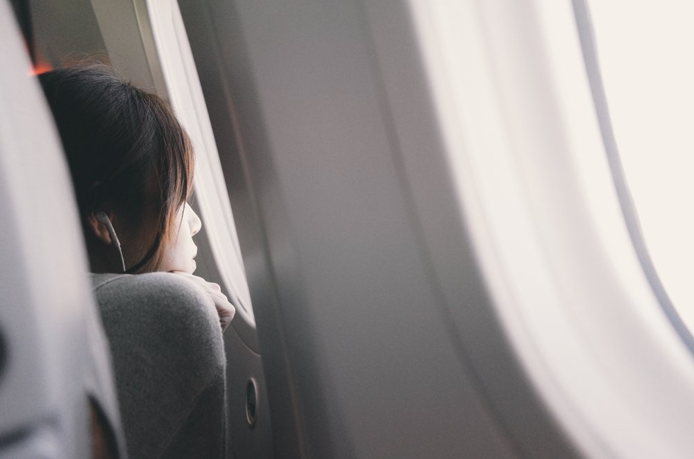 Woman looking out airplane window