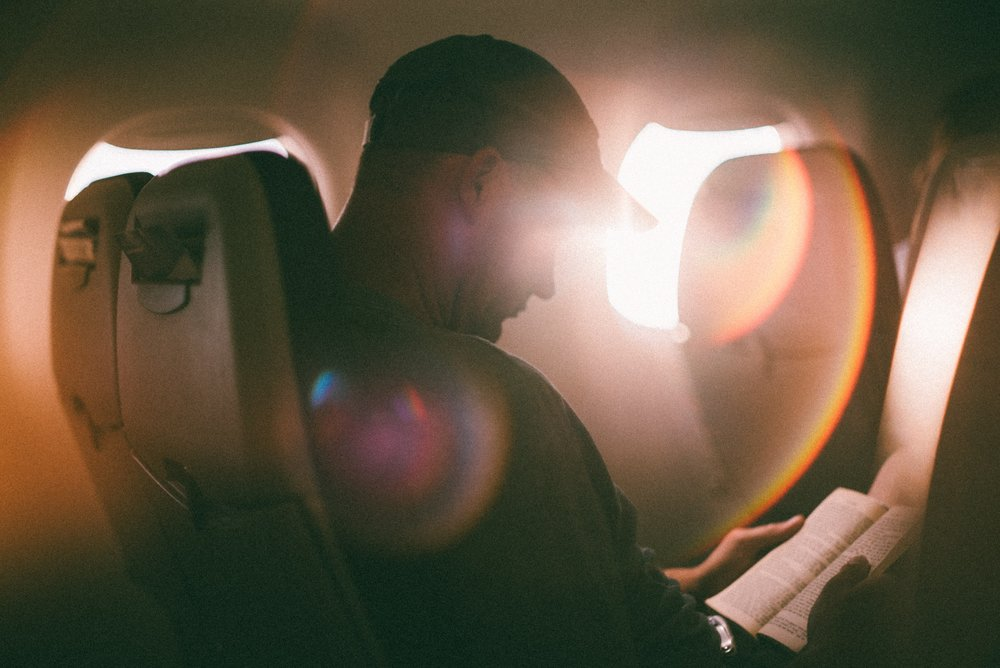 Man reading book on flight with sunlight behind