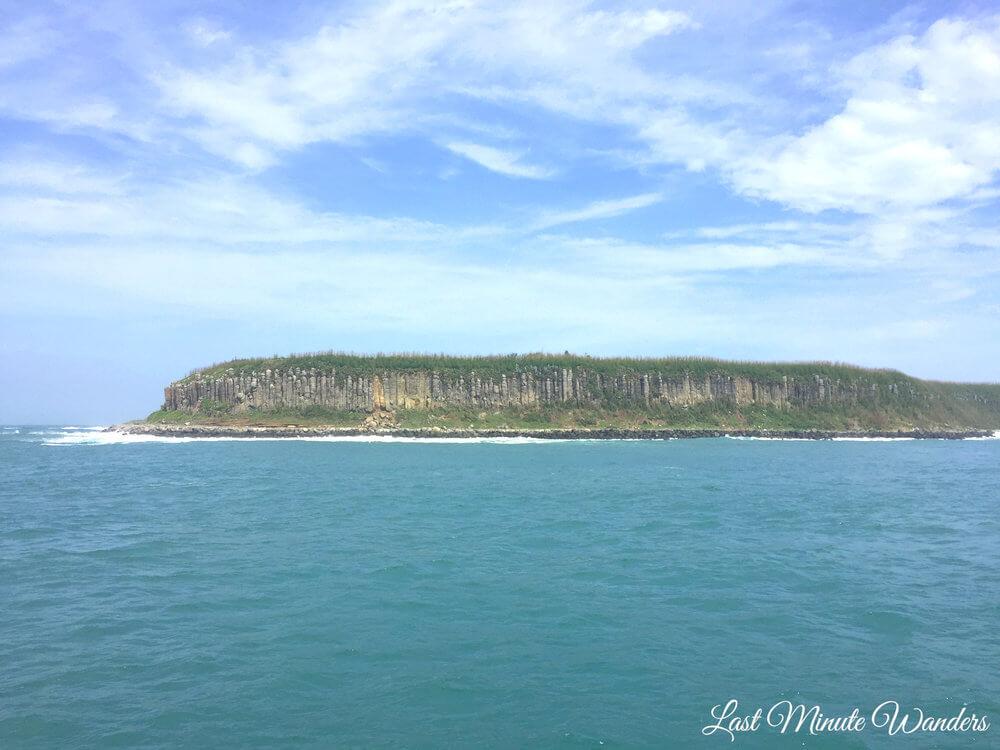 An island of basalt columns viewed from sea