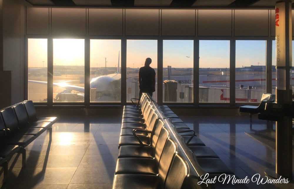 Man standing at window in empty airport lounge