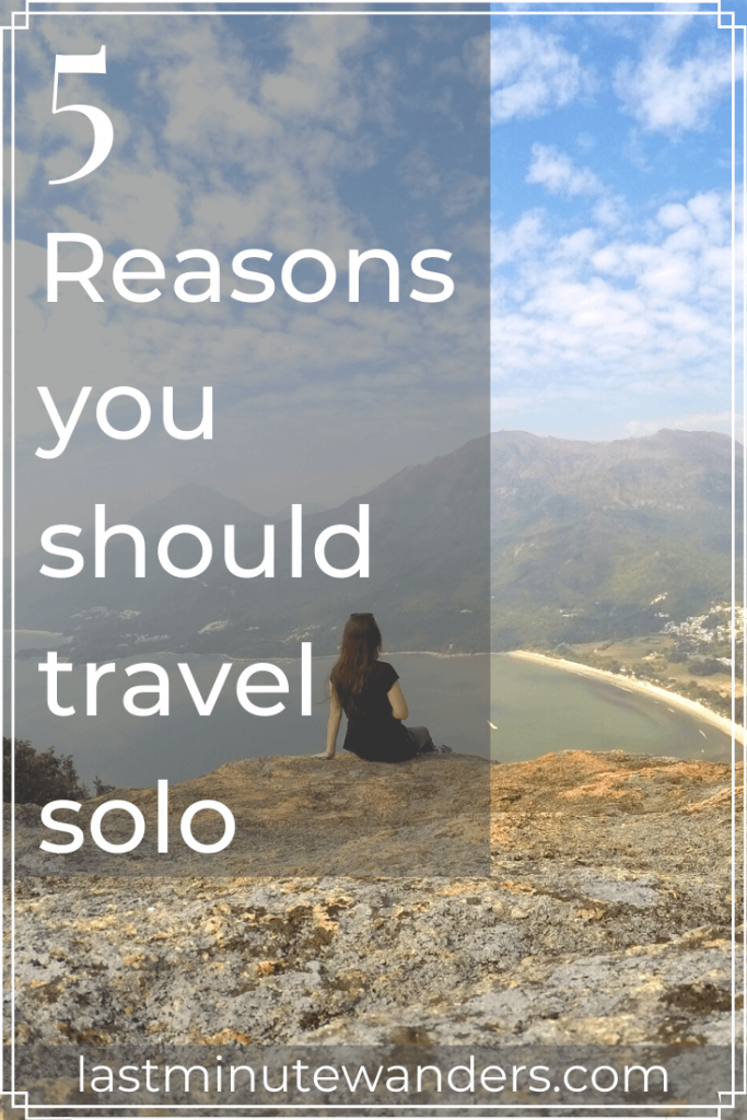 Woman sat on rock on mountain looking at view with text overlay - 5 reasons you should travel solo