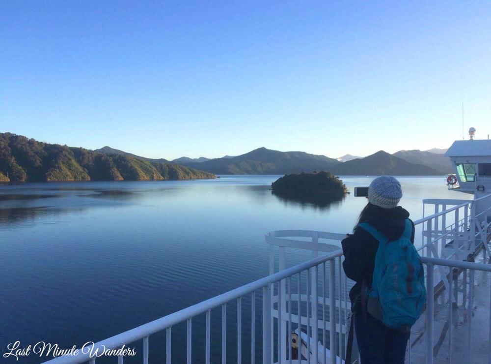 Woman on ferry taking photo of mountains
