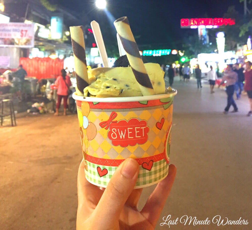 Hand holding tub of ice cream with wafers