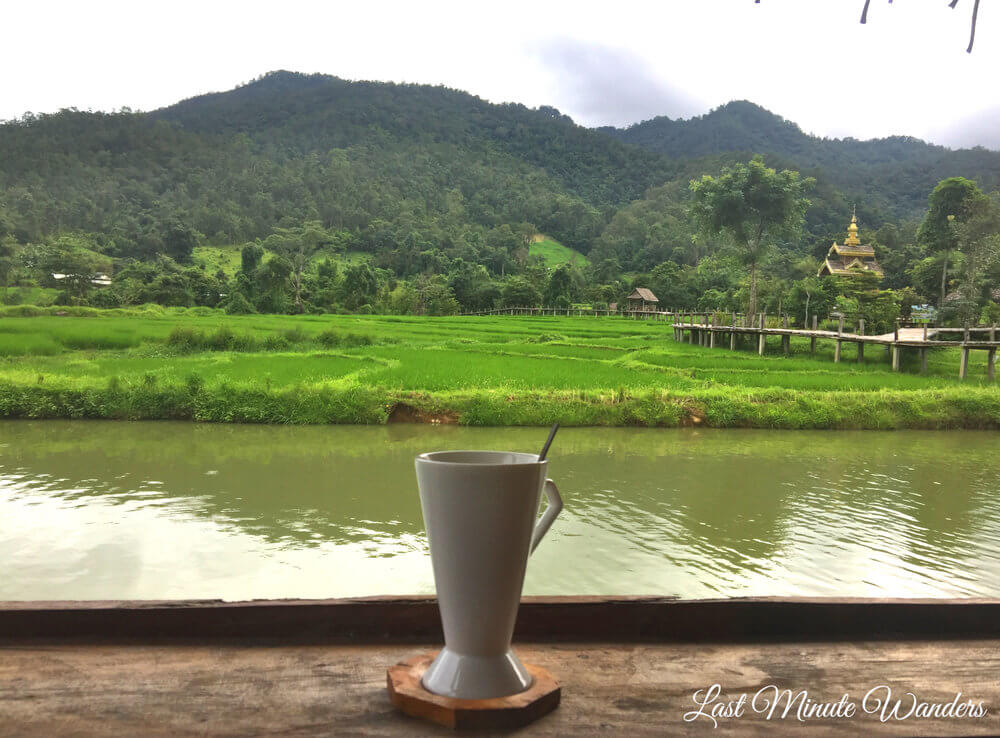 Coffee on table with view of mountains and rice fields