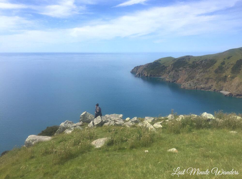Man sat on rock looking at sea view