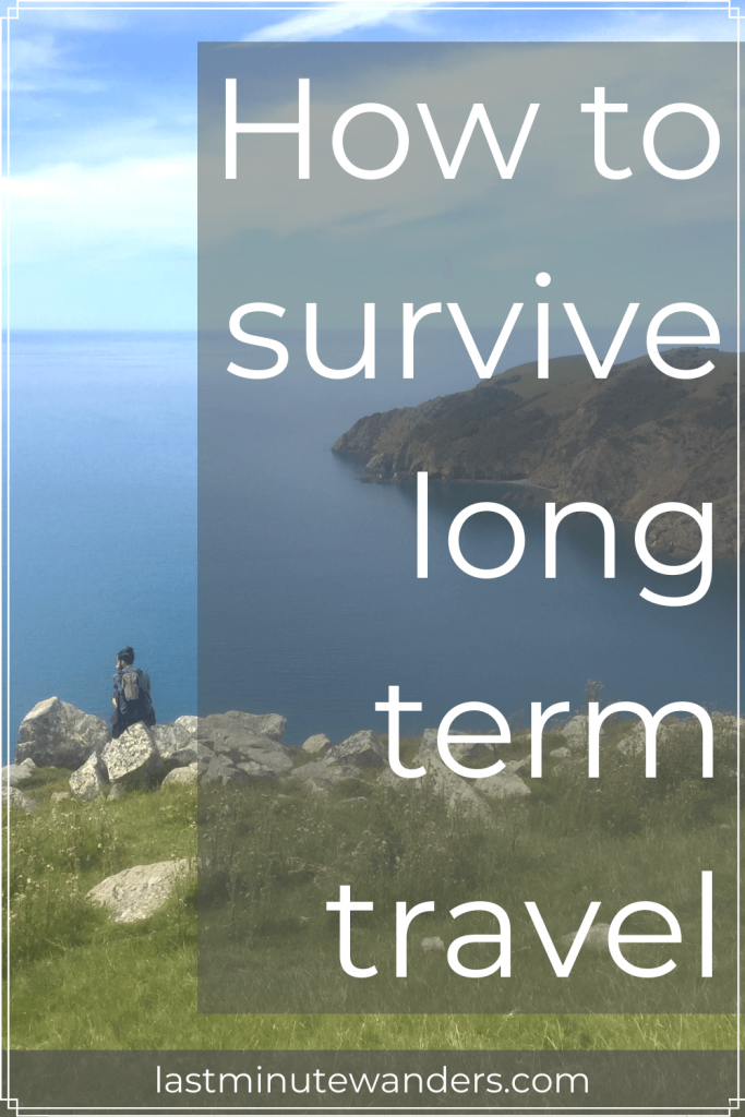 Man on rocks on cliff looking at ocean with text overlay - How to survive long term travel