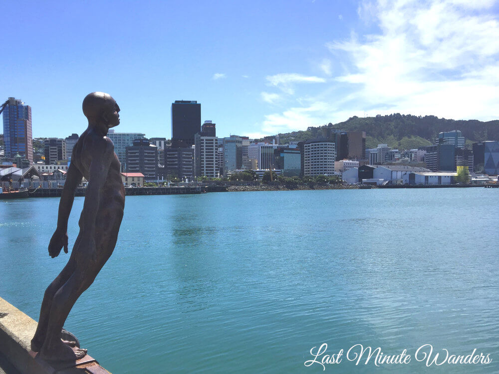 Statue of man leaning over water with city in background