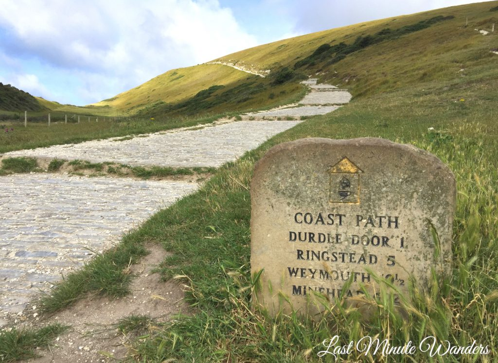 Path leading up hill and stone sign