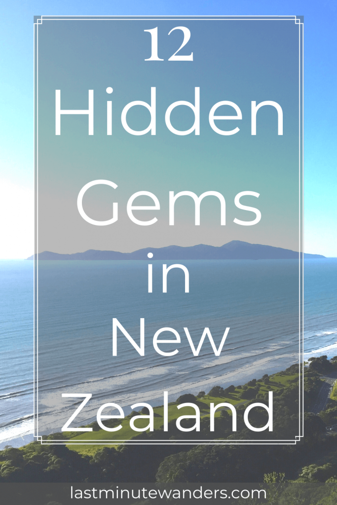 View from hillside of curved coast and hilly island with text overlay - 12 hidden gems in New Zealand