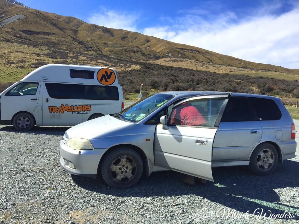 Silver car with front door open next to Travellers Autobahn campervan with mountain in the background