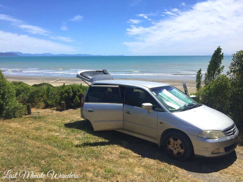 Silver car with back doors open parked on grass in front of the ocean