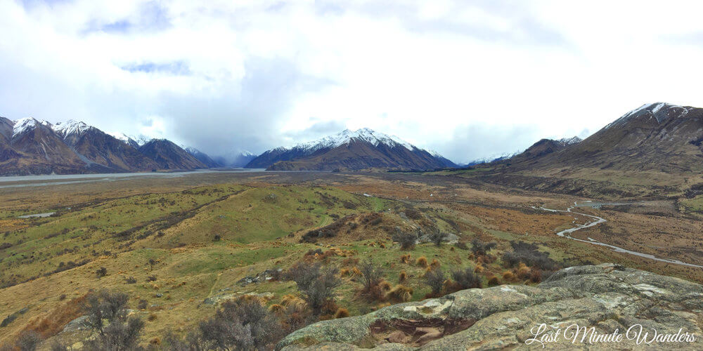 Wide grassy valley with streams running through and snow-capped mountains ahead and to the sides
