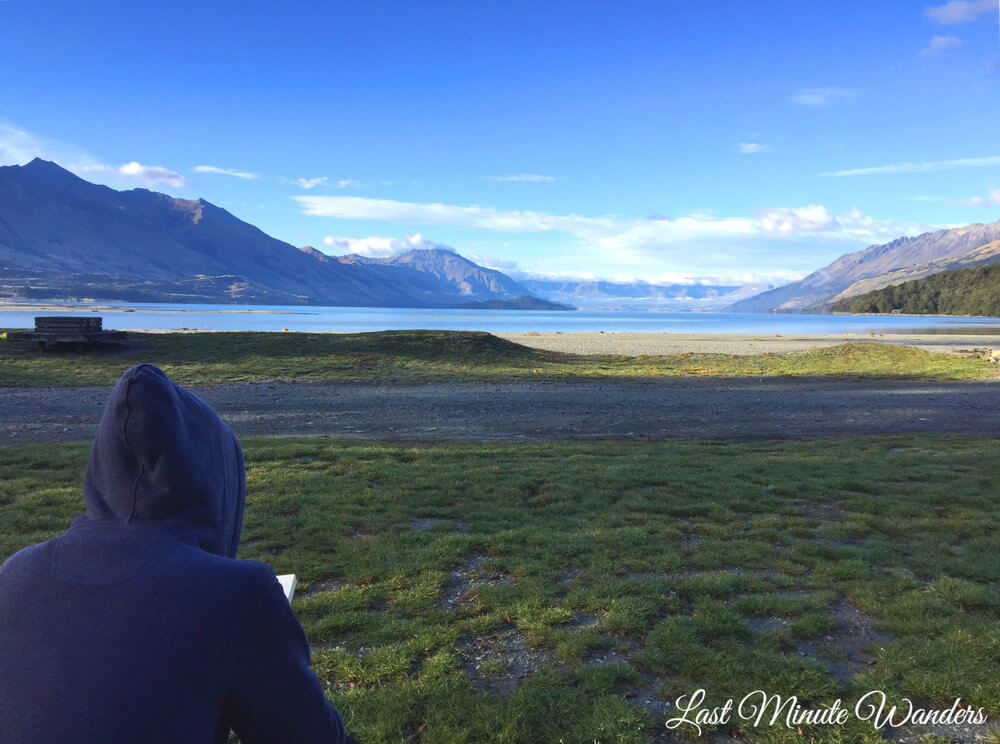 Person in hooded jacket reading book in front of beautiful view of mountains and lake