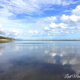 View down wet beach, reflecting the blue sky and white clouds