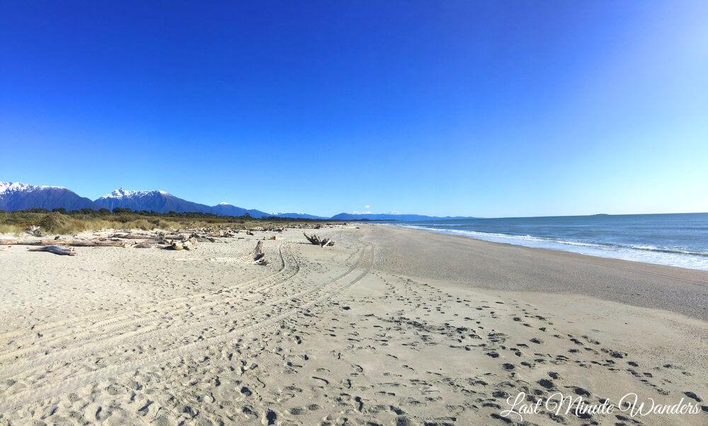 Looking down a sandy beach with the blue ocean on the right and mountains on the left