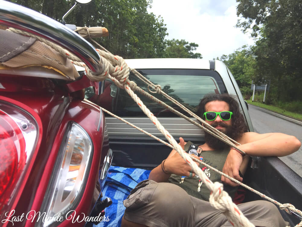 Man with long hair and green sunglasses sitting in back of pickup truck. He's surrounded by ropes and you can see the moped that they are tying down, also in the back of the truck.